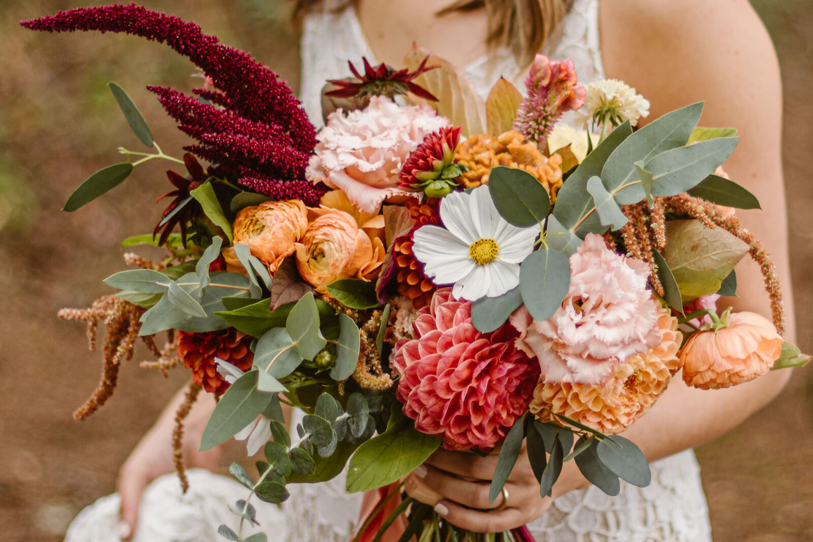 Bride carries floral bouquet down the trail to get married